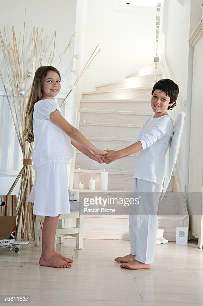 christmas day, girl and boy posing for the camera, holding their hands each others, indoors - christkind stock-fotos und bilder