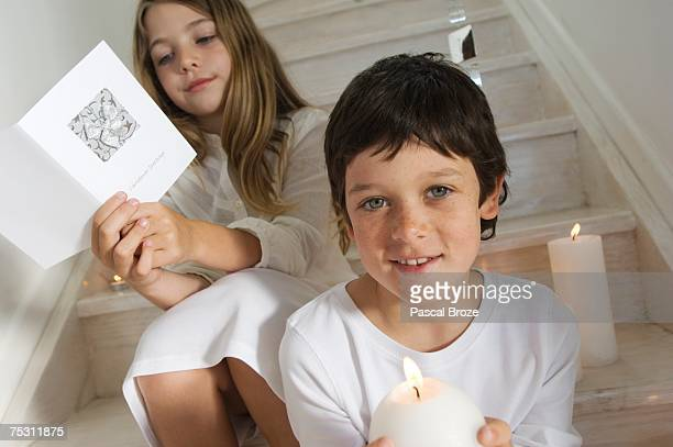 Christmas day, portrait of a little boy holding a candle, girl in background reading a card, indoors