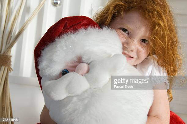 christmas day, portrait of a little girl holding a cuddly toy (santa claus), indoors - dead girl stock pictures, royalty-free photos & images