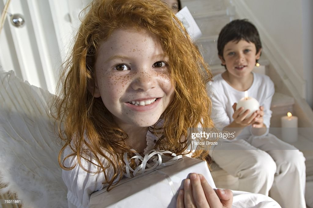 Christmas day, portrait of a little girl holding a present, little boy in background, indoors : Stock-Foto