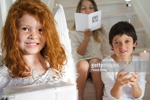 Christmas day, portrait of a little girl holding a present, sister and brother in background with card and candle, indoors