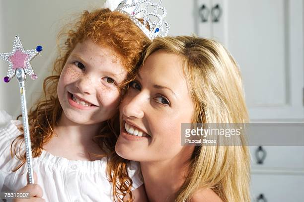 Christmas day, portrait of a mother and daughter smiling, looking at the camera, indoors