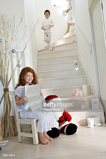 Christmas day, three children holding a present, one posing for the camera, two on the stair, indoors