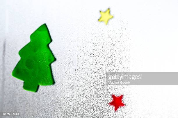 Christmas decals on a window with condensation on it, close-up