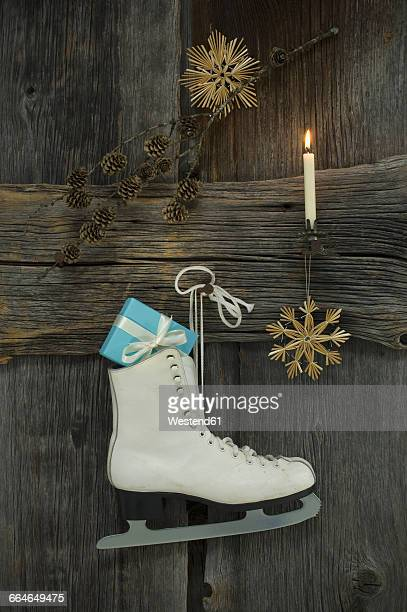 Christmas decoration and ice kate with present hanging on wooden wall