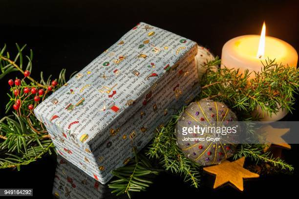 Christmas decoration, box with colourful Christmas theme, lit candle, hand felted and embroidered bauble, yellow felt stars and branches, black background