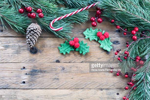 Christmas decoration:  Crochet mistletoe leaves, candy cane, pine cone, fir tree branches, and mistletoe seed on rustic wooden background. Top view and copy space.
