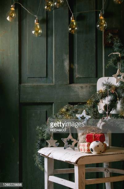 Christmas decoration fir tree branches. Ceramic stars. Luminous garland. Gift boxes in craft paper on vintage white chair with wooden door at...