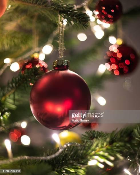 weihnachtsdekoration. hängen rote kugeln auf kiefer zweige weihnachtsbaum girlande und ornamente über abstrakte bokeh hintergrund mit kopierraum - spielball stock-fotos und bilder