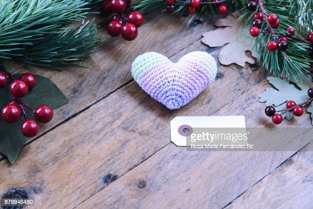 Christmas decoration: Heart shape crochet and blank greeting card framed with fir tree branches,  leaves and mistletoe seed on wooden background. Selective focus and copy space.