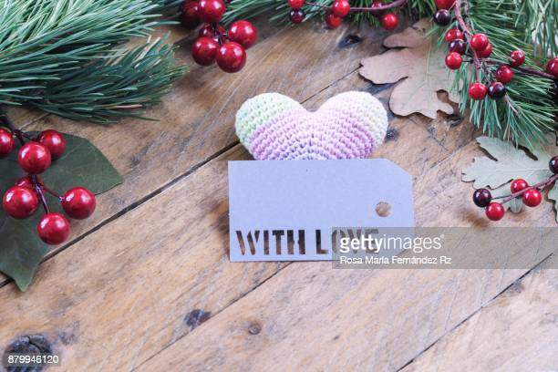 Christmas decoration: Heart shape crochet, greeting card with the word 'with love' written framed with fir tree branches,  leaves and mistletoe seed on wooden background. Selective focus and copy space.