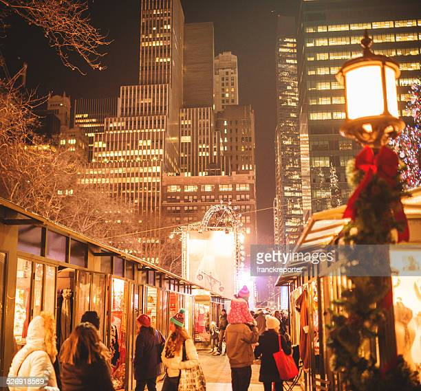 New York City, New York, USA - December 26, 2013: People walking at the Bryant Park christmas market during the annual christmas holiday . The park is open even in the evening with many shop and traditional stalls . New york city downtown.