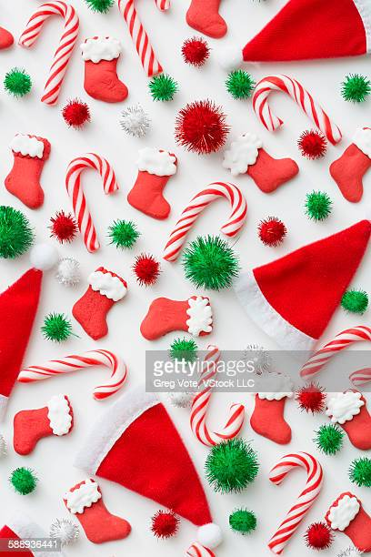 christmas decoration of santa hats, candy canes and christmas stockings - pom pom stock pictures, royalty-free photos & images