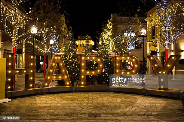 Christmas decoration on the street with big HAPPY letters illuminated with lights during shopping days at the city.