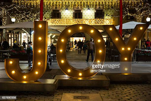 Christmas decoration on the street with big JOY letters illuminated with lights during shopping days at the city.