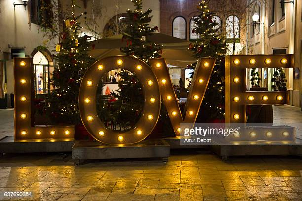 Christmas decoration on the street with big LOVE letters illuminated with lights during shopping days at the city.