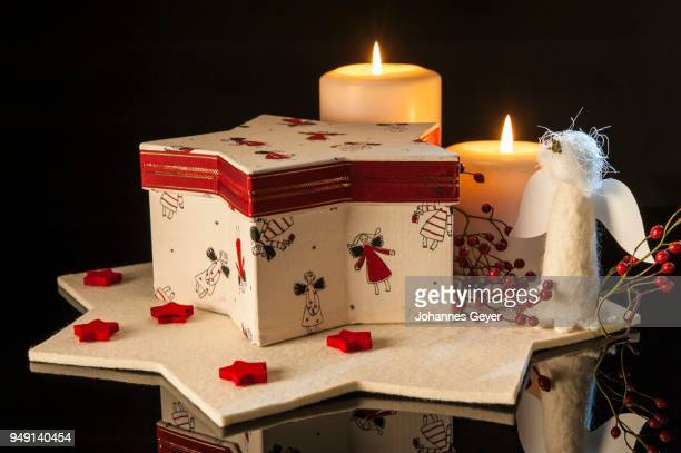 Christmas decoration, red and white star-shaped box with angels on, two lit candles, felted star, black background
