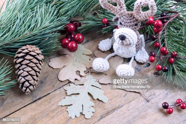 Christmas decoration: Reindeer in crochet and pine cone framed with fir tree branches and mistletoe seed on rustic wooden background. Selective focus and copy space.