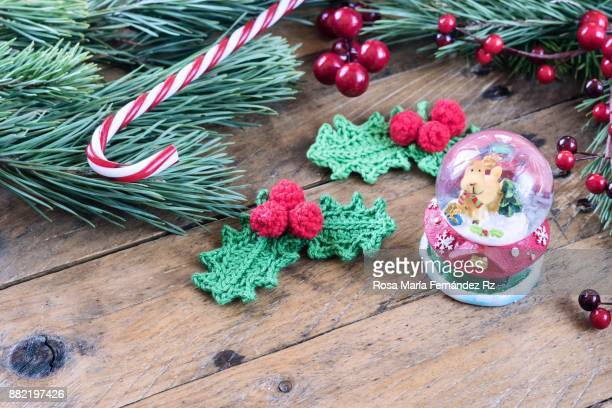 Christmas decoration: Santa's Magic Crystal Ball with reindeer inside, crochet mistletoe leaves, candy cane, fir tree branches and mistletoe seed on rustic wooden background.Selective focus and copy space.