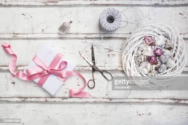 Christmas decoration, scissors and Christmas present on wood