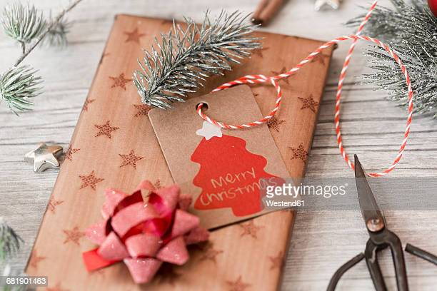 Christmas decoration, scissors and wrapped presents on wood