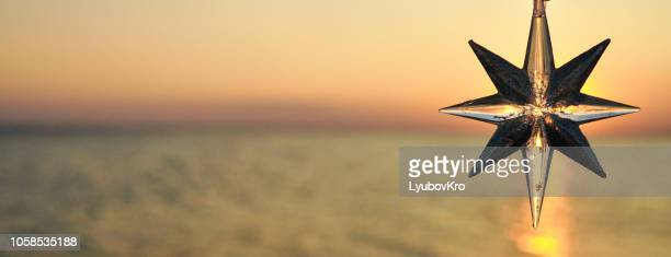 christmas decoration star on the background of the sunset on the sea. banner. - hello december stock pictures, royalty-free photos & images
