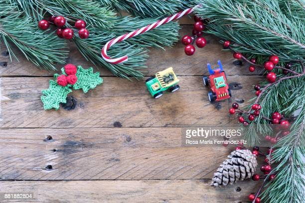 Christmas decoration: Toys, Crochet mistletoe leaves, candy cane, pine cone, fir tree branches, and mistletoe seed on rustic wooden background. Top view and copy space.