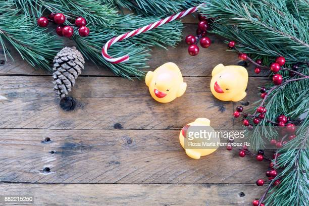 Christmas decoration: Toys, fir tree branches, mistletoe seed, candy cane and  pine cone on rustic wooden background. Top view and copy space.
