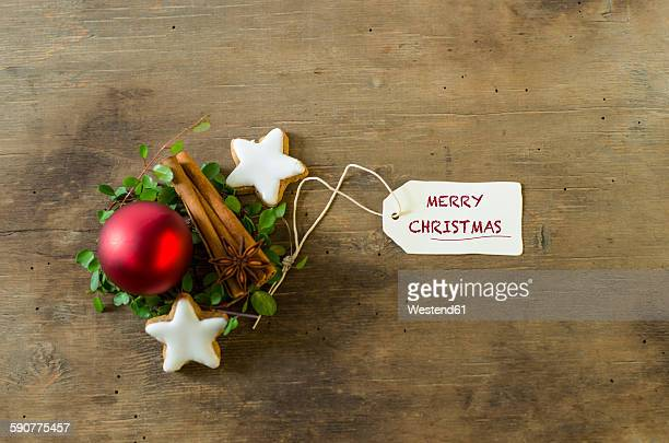 Christmas decoration with cinnamon sticks and stars and a red Christmas bauble on wood