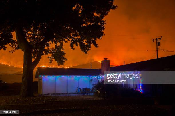 Christmas decorations illuminate a house as the growing Thomas Fire advances toward Santa Barbara County seaside communities on December 10 2017 in...