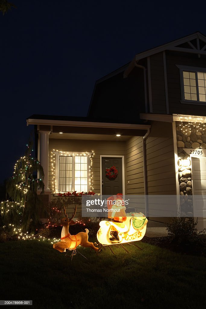 Christmas Decorations Illuminated On Lawn In Front Of House Night