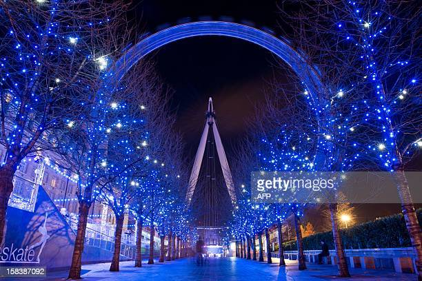 Christmas decorations in the trees light up the path leading towards the London Eye in central London on December 14 2012 Areas of central london are...