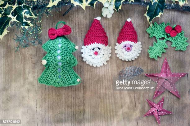Christmas decorations made in crochet and origami framed with holly leaves. Top view and copy space on wooden background. Top view.