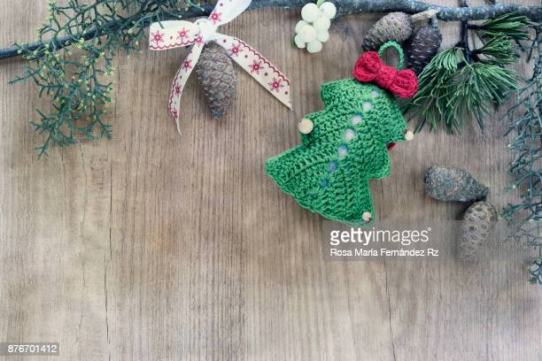 Christmas decorations made in crochet framed with fir tree and pine cone. Top view and copy space on wooden background. Top view.