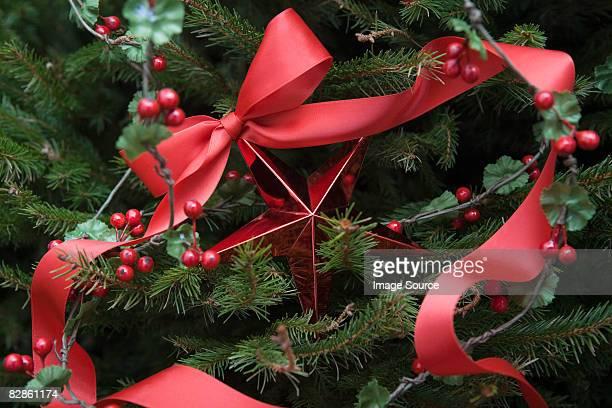 christmas decorations on a tree - holly stockfoto's en -beelden