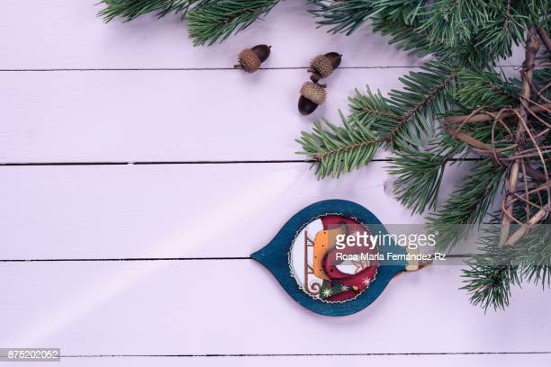 Christmas decorations: Santa Claus and star shape, fir tree, pine cone with copy space on wooden background. Directly above.