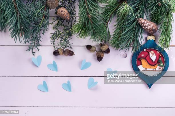 Christmas decorations: Santa Claus and star shape, fir tree, pine cone and acorn with copy space on wooden background. Directly above.