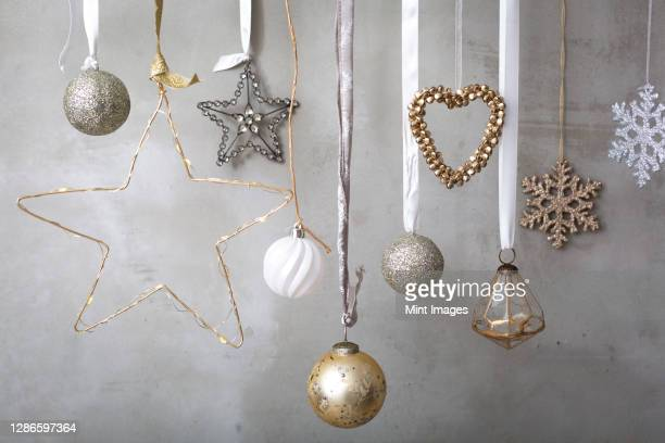 christmas decorations, silver, white and gold baubles on ribbons on grey background. - christmas bauble stock pictures, royalty-free photos & images