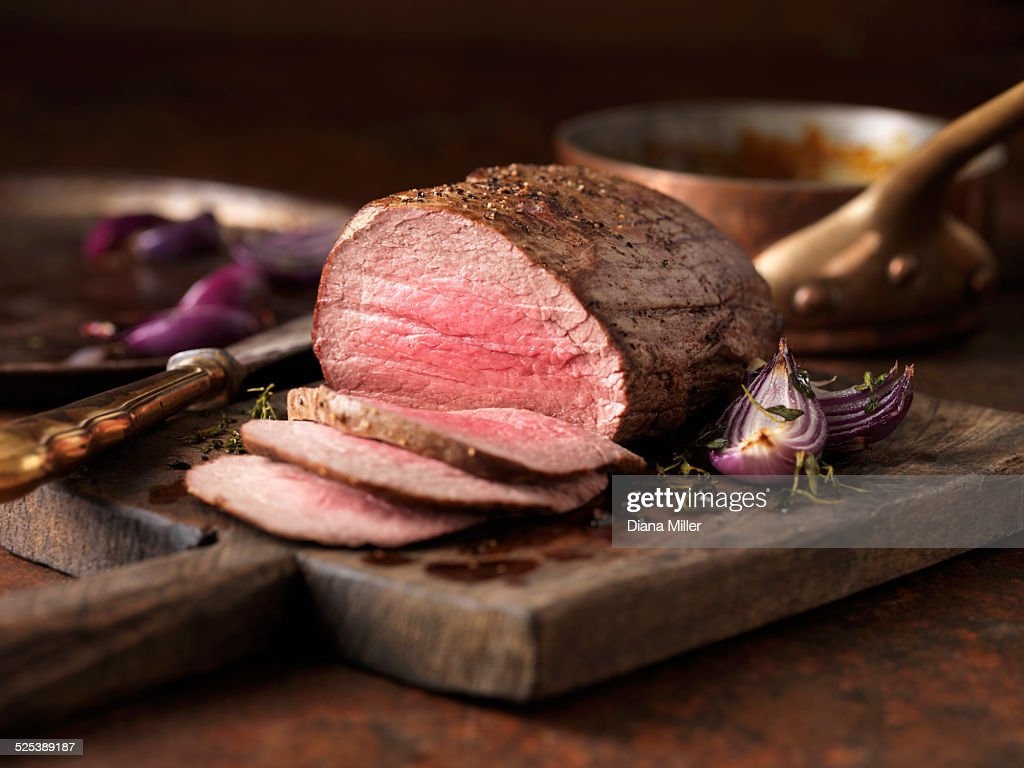 Christmas dinner. Chateaubriand steak cooked with a thick cut from the tenderloin filet, rare medium served with roasted onions, pepper and herbs : Stock Photo