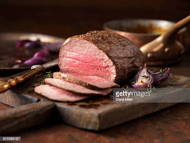 christmas dinner. chateaubriand steak cooked with a thick cut from the tenderloin filet, rare medium served with roasted onions, pepper and herbs - meat stock pictures, royalty-free photos & images