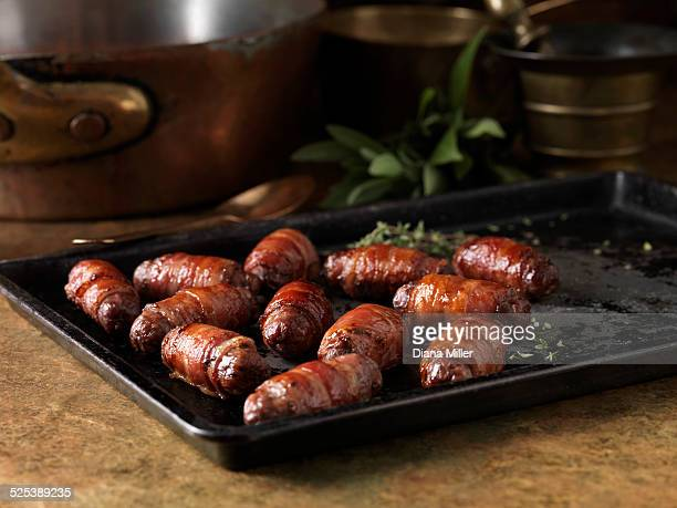 christmas dinner snack. festive spiced bacon and venison cocktail sausage rolls. pigs in blankets with thyme bay leaves - sausage stock photos and pictures