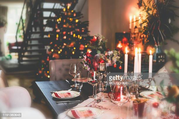 christmas dinner table at festive cozy room background with christmas tree - noël photos et images de collection