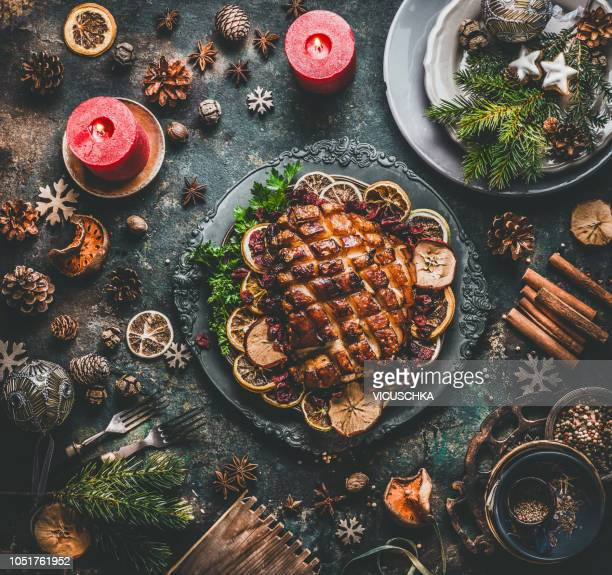 christmas dinner table with roasted pork ham , flavors, decoration and candles - evening meal stock pictures, royalty-free photos & images