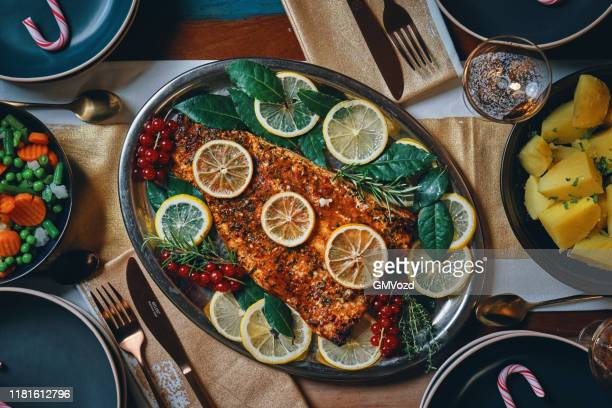 christmas dinner with salmon fish fillet, vegetables, polenta and christmas cake - fish stock pictures, royalty-free photos & images