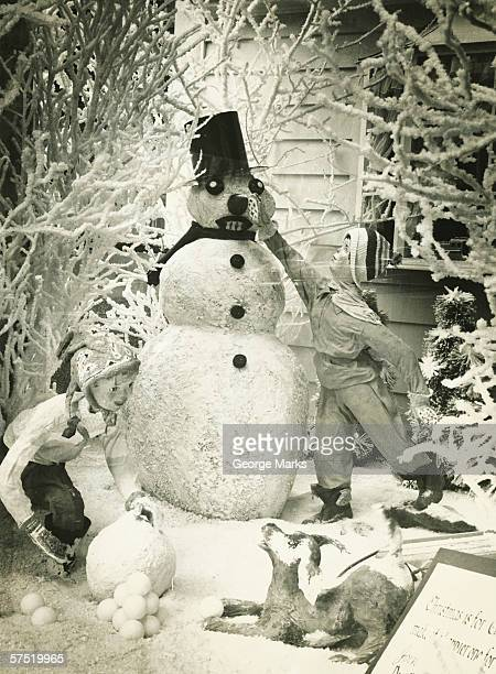 christmas display with snowman in garden, (b&w) - 20th century stock pictures, royalty-free photos & images