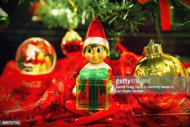 Christmas elf character holding a present under a Christmas tree