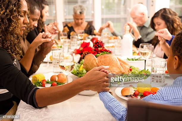 christmas:  family prays before eating holiday dinner. - national day of prayer stock photos and pictures