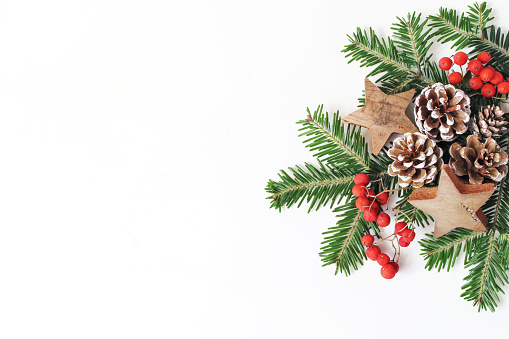 Christmas festive styled floral composition. Pine cones, fir tree branches, red rowan berries and wooden stars on white table background. Decorative frame, web banner. Flat lay, top view. Copy space. 1051258812