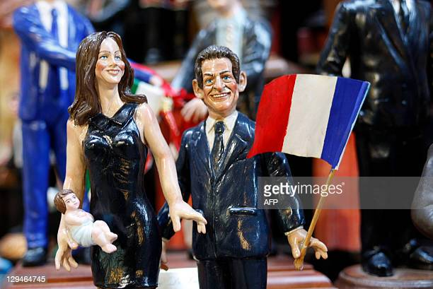 Christmas figurines depicting French President Nicolas Sarkozy and his wife Carla Bruni with their newborn are on display at the workshop of artist...