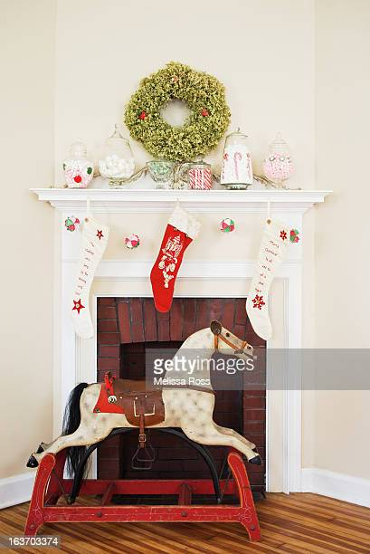 christmas fireplace display with rocking horse - christmas horse stock pictures, royalty-free photos & images